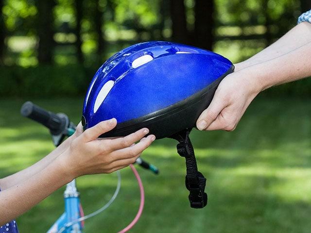 Bike Impossible, Adult handing a child a bike helmet