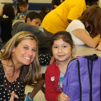 Stuff-It! Backpacks for Charity, woman and a child with backpacks
