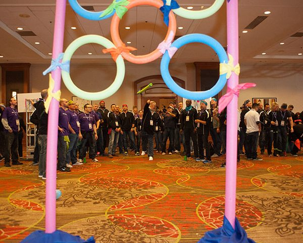 Indoor Field Day, group of people throwing something through circle balloons