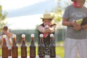 Outlaw Olympics, water gun shooting balls off bottles
