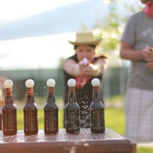 Outlaw Olympics, person shooting balls off of bottles